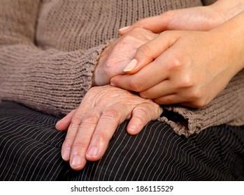 Nurse holding elderly wrinkled hand
