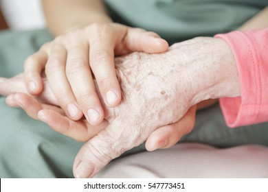Nurse holding the hand of an elderly woman - closeup detail image.