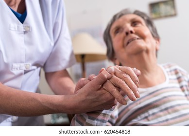 Nurse holding the hand of an old woman