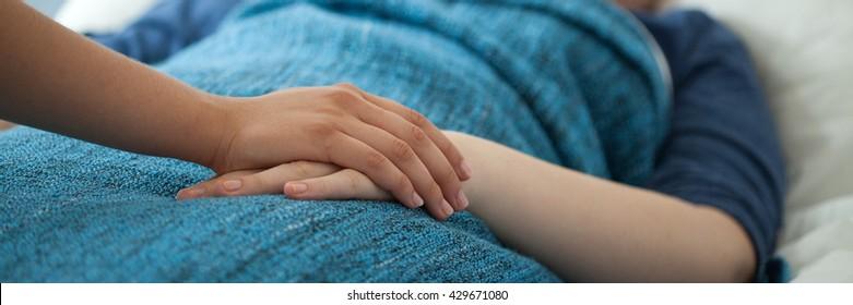 Nurse holding hand of woman having carcinoma