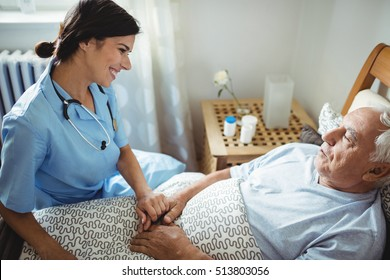 Nurse holding hands of senior man in bedroom