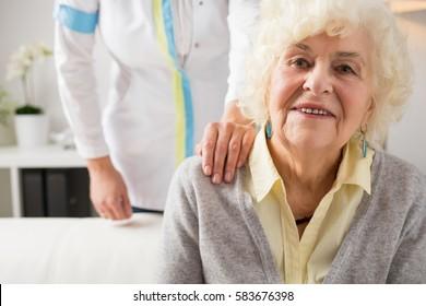 Nurse holding her hand on elderly womans shoulder