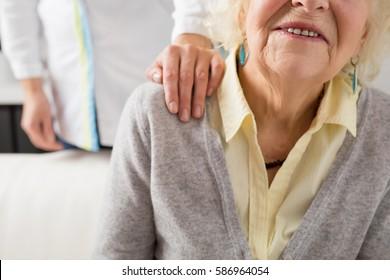 Nurse holding her hand on seniors shoulder