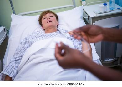 Nurse holding iv drip in hospital room