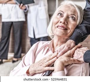 Nurse holding senior woman's hand in hospital. Healthcare concept.