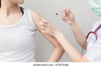 Nurse holding a syringe with a liquid inside next to a female arm.