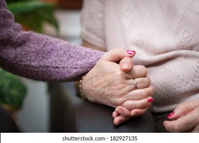 Nurse holds the senior woman hands
