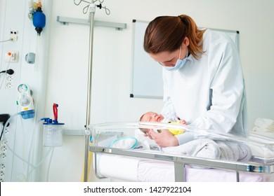 Nurse in ICU examining premature born infant