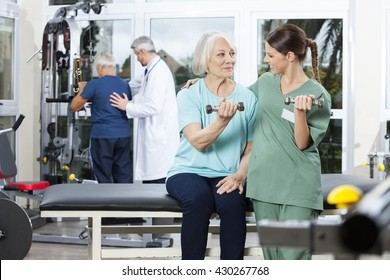 Nurse Instructing Senior Patient Exercising With Dumbbell