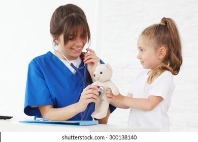 nurse and kid examining teddybear
