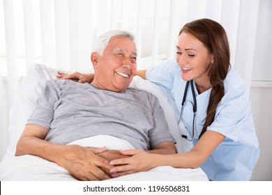 Nurse Looking At Happy Male Patient Lying On Bed In Clinic