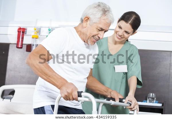 Nurse Looking At Patient Using Walker In Rehab Center