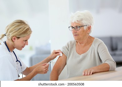 Nurse making vaccine injection to elderly patient