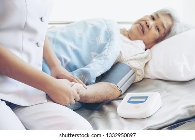 nurse measuring blood pressure of senior elderly woman in hospital bed patients - medical and healthcare senior concept