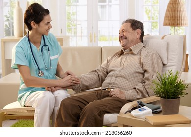 Nurse measuring blood pressure of senior man at home. Smiling to each other.