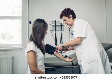 Nurse measuring her patient's heart pressure. Interacting and taking care of patient. Taking care of your health. Disease prevention.