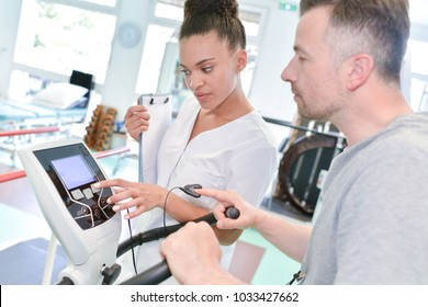 nurse measuring patients blood pressure during exercise electrocardiography