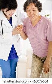 Nurse in nursing home helping senior woman stand up