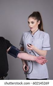 Nurse with open mouth as she checks blood pressure monitor on a patient