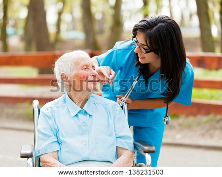 Nurse outdoors helping elderly lady in wheelchair.