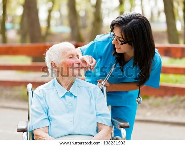 Nurse outdoors helping elderly lady in wheelchair.
