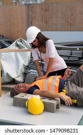 Nurse or paramedic providing cardiopulmonary resuscitation (CPR) on a construction worker injured in an accident at work. Outdoors