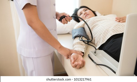 Nurse with patient. Routine health check with blood pressure reader. Female nurse with senior chinese woman.