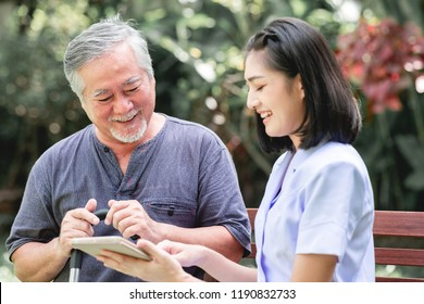 Nurse with patient sitting on bench together looking at tablet. Asian old man and young woman sitting together talking. Relax mood.