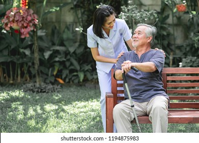 Nurse with patient sitting on bench together talking. Asian old man sitting on bench and young woman carer talking to him. Happy smile.