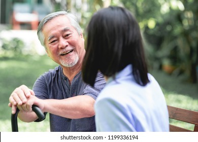Nurse with patient sitting on bench together talking. Asian old man and young woman sitting together talking. Happy smile.