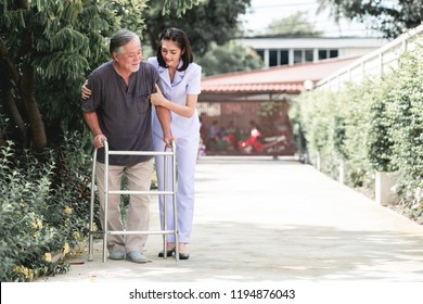 Nurse with patient using walker in retirement home. Young female nurse holding old man's shoulder in outdoor garden walking. Senior care, care taker and senior retirement home service concept.
