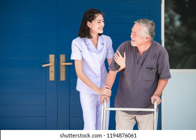 Nurse with patient using walker in retirement home. Young female nurse holding old man's shoulder in front of senior home. Senior care, care taker and senior retirement home service concept.