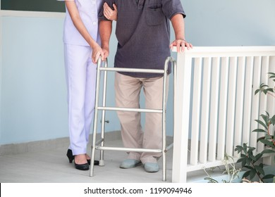 Nurse with patient using walker in retirement home. Young female nurse holding old man's hand in front of senior home. Senior care, care taker and senior retirement home service concept.