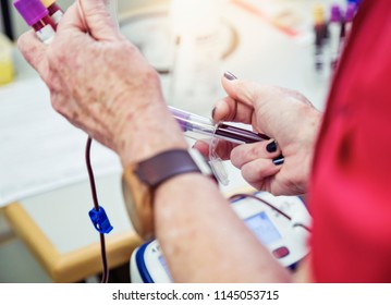 A nurse, phlebotomist, or technician checks the blood collection bag emerging from the donor's arm via plastic tubing, holding vials of collected blood..