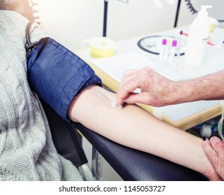 A nurse, phlebotomist, or technician, wipes a female blood donor's arm with a sterile swab.