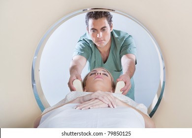 Nurse preparing young woman for CT scan test