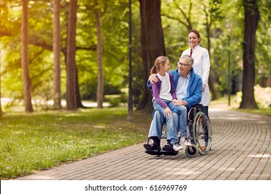 nurse pushing senior man on wheelchair with his granddaughter in park