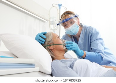 Die Krankenschwester stellt eine Sauerstoffmaske auf ältere Patientinnen, die im Krankenhausschlafzimmer liegen, und trägt Schutzhandschuhe und ärztliche Schutzmaske, das Schutzkonzept Coronavirus covid 19