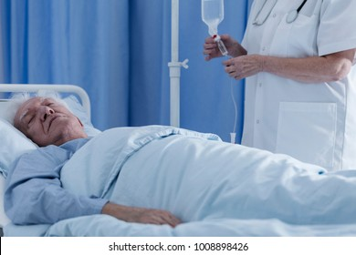 Nurse putting a dying, senior patient on a drip in a hospital