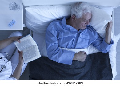Nurse reading for lonely and suffering patient in hospital room