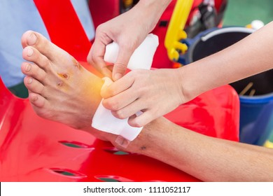 Nurse receiving first aid wounding bandage bruised wound injury on foot of patient