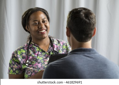 Nurse receiving medical history from male patient