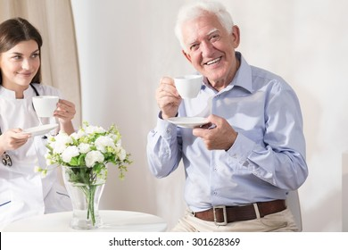 Nurse and retiree drinking coffee at home