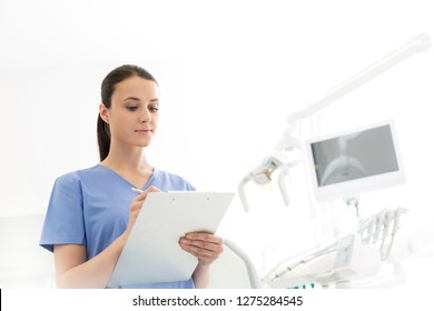 Nurse reviewing medical report on clipboard at dental clinic