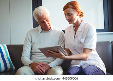 Nurse and senior man using a digital tablet in a retirement home