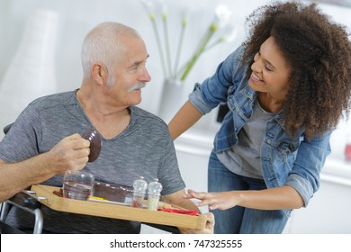 nurse serving breakfast to senior man at home