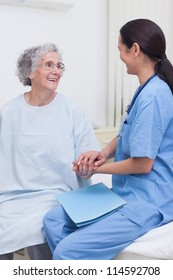 Nurse sitting on bed with a patient in hospital ward