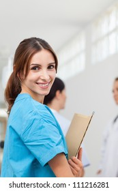 Nurse smiling while holding files and standing with a doctor and a patient in a hallway