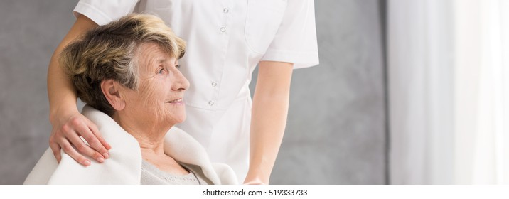 Nurse standing behind the senior woman looking at the bright window with the hand on elder woman's shoulder