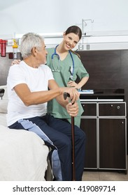 Nurse Standing By Senior On Bed In Rehab Center